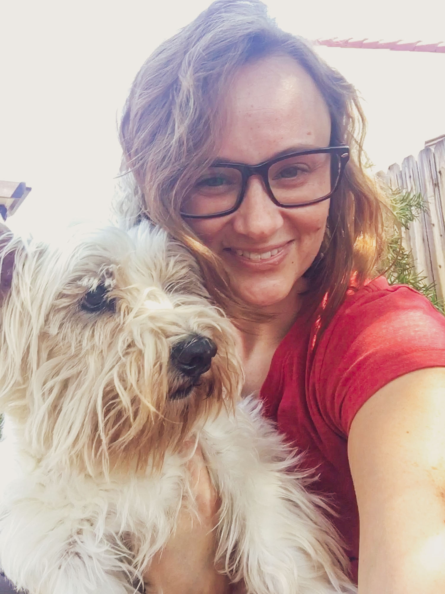 A portrait of the author, Megan, holding her dog Shay.
