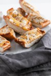 This Ultimate Cheesy Garlic Bread is the perfect addition to dinner tonight. Buttery garlic bread smothered in three cheeses and Italian seasoning.