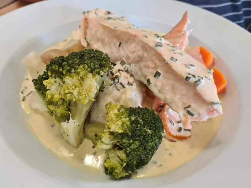 Salmon in a white wine sauce with vegetables