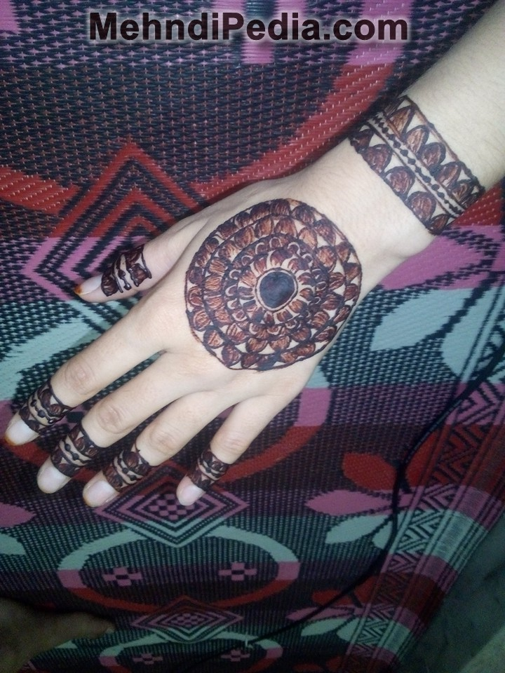 Centrally placed circular henna design for back and front hand