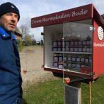 Mann steht vor kleiner Bude mit lauter Marmeladengläsern