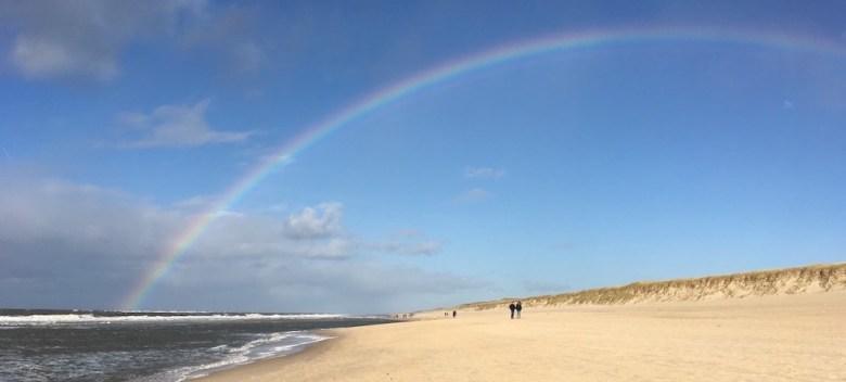Spaziergänger am Strand mit Regenbogen