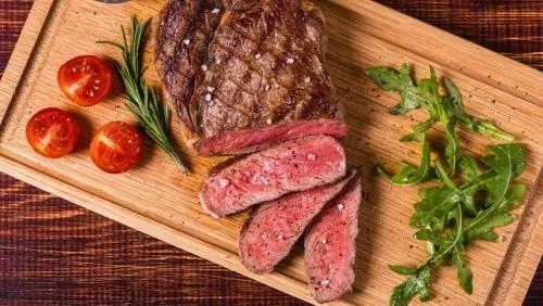 Carne en una tabla con verduras.