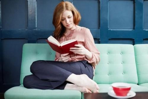Mujer leyendo un libro sentada en un sofá.