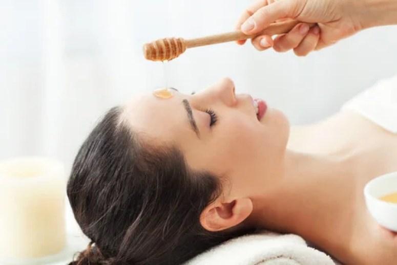Mujer siendo tratada con miel en la cara.