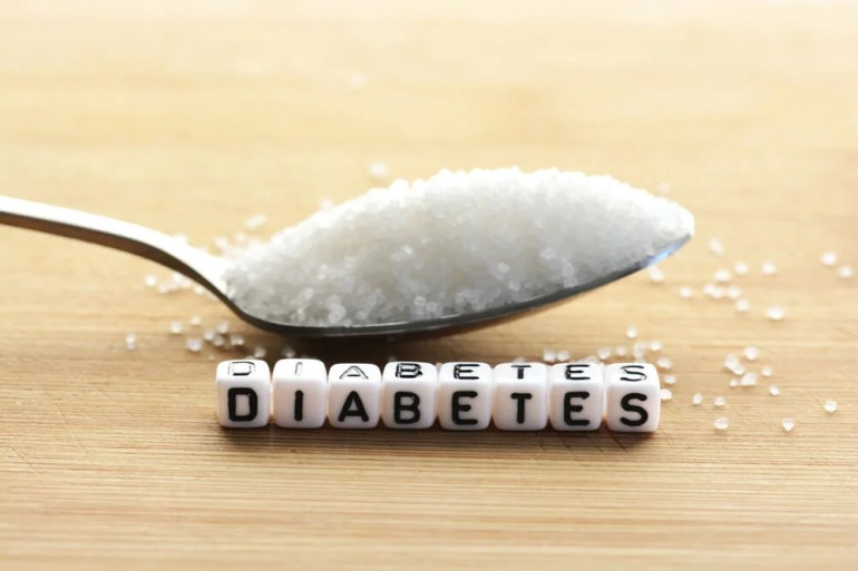 Cucharada de azúcar y letras formando la palabra DIABETES