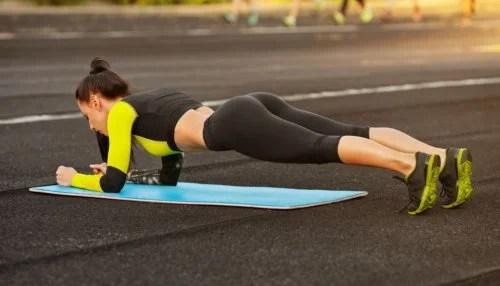 Mujer realizando abdominales en plancha en el exterior.