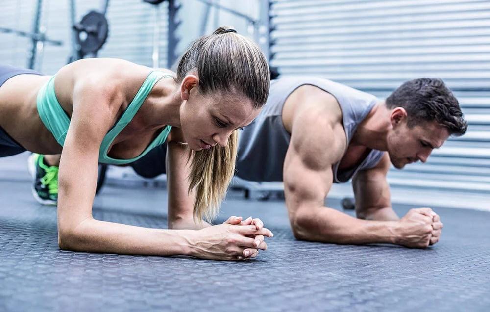 Pareja de deportistas haciendo una plancha en el gimnasio