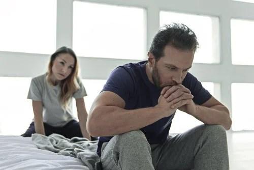Hombre pensativo sentado en la cama mientras su mujer le mira preocupada.