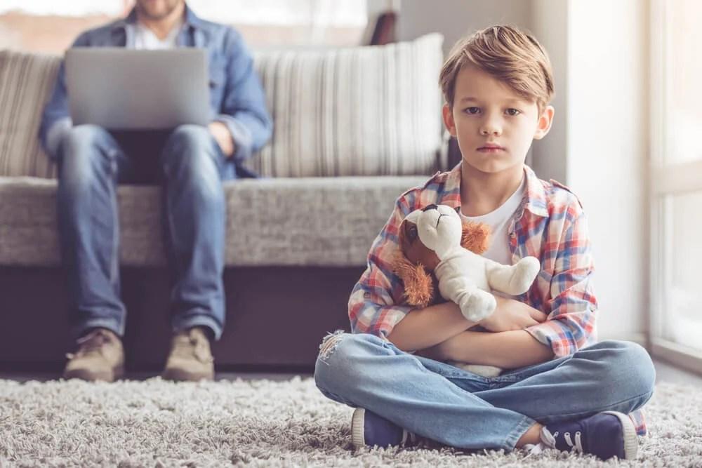 Niño sentado en la alfombra mientras su padre trabaja con el ordenador.