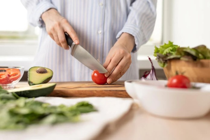 Mujer cortando alimentos frescos