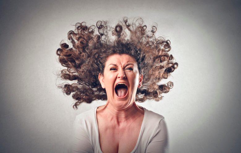 Frau schreit sich in rasender Wut die Kehle aus dem Leib und ihre lockigen Haare fliegen wild um ihren Kopf herum.