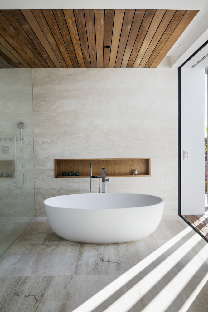 The cladded wood ceiling gives this neutral bathroom a Scandinavian sauna feel Credit:  ArchDaily