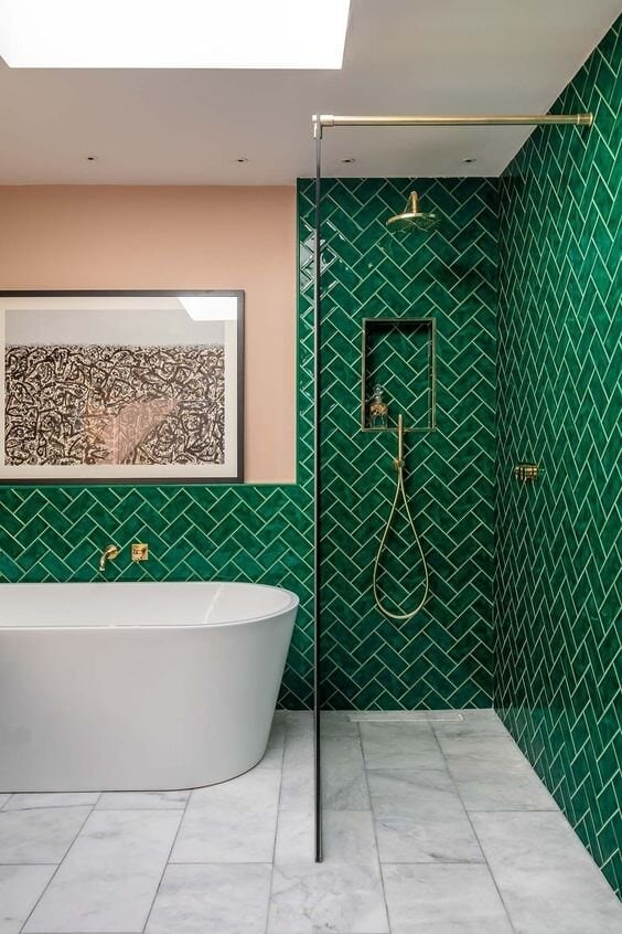 In this bathroom they have used green metro tiles on the wall and painted the wall opposite a salmon pink. Credit: barlowandbarlow.com
