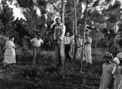 The body of 32-year-old Rubin Stacy hangs from a tree in Fort Lauderdale, Fla., as neighbors visit the site July 19, 1935. Stacy was lynched by a mob of masked men who seized him from the custody of sheriff's deputies for allegedly attacking a white woman. (AP Photo)
