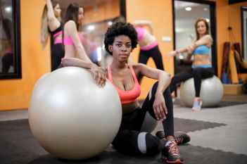 young ethnic woman with fit ball sitting on floor while training in modern gym