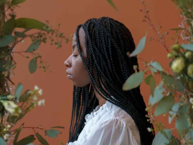 confident black lady with closed eyes near frame with plants