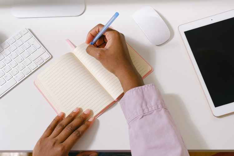 black woman with pen taking notes in planner