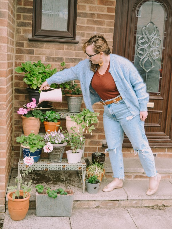 River Island ripped jeans and Sezane knitwear jumper and LK Bennet pumps watering flowers on porch