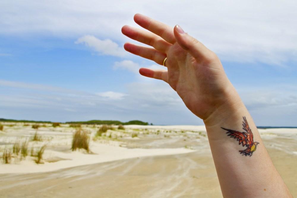 foto de tatuagem de passaro no braco com fundo de areia