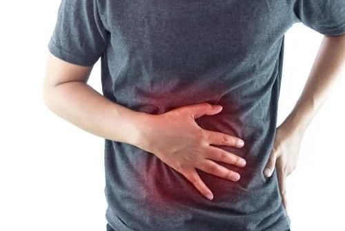 Pessoa com dor de estômago após se submeter a um bypass gástrico