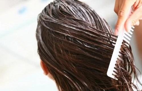 Mulher colocando creme para evitar problemas de cabelo