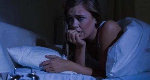Mulher com ataque de pânico deitada na cama