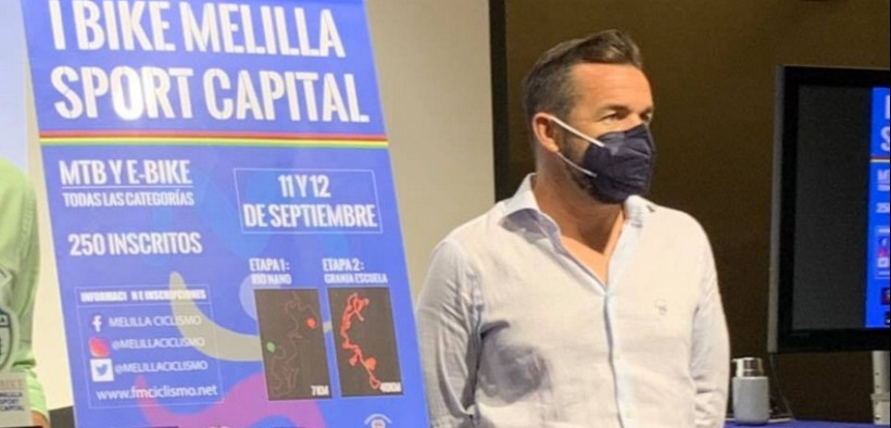 Javier Iglesias, presidente de la Federación Melillense de Ciclismo, junto al cartel anunciador de la prueba