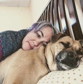 Picture of the author and her puppy dog lying on the bed.