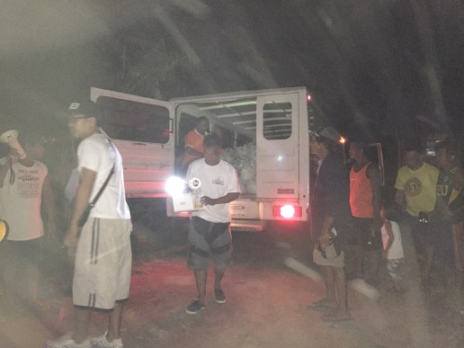 The truck arrives and begins distributing food packs.