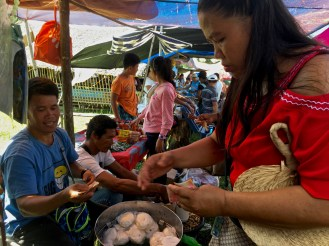 em buys siopai from a street vendor