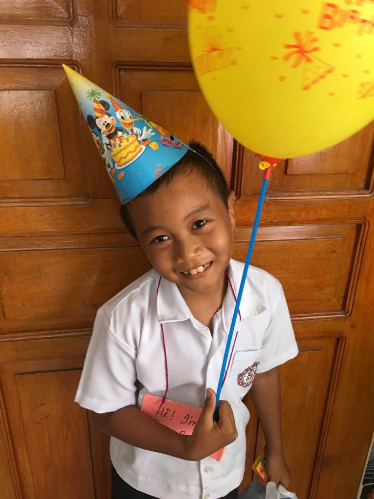 little kid in a party hat and birthday balloon