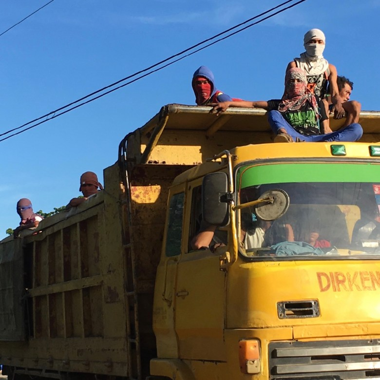 workman travel on the top of a truck in the Philippines