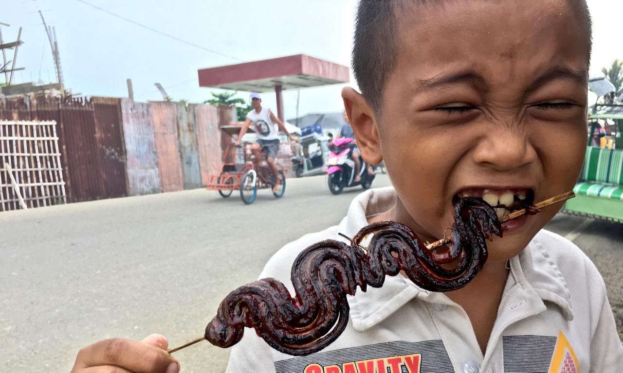 Filipino boy eating BBQ stick of eels