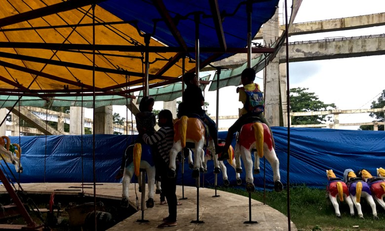 kids on a dilapidated merry go round
