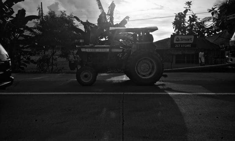 three men in a tractor black and white
