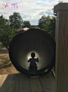 toddler boy in a tunnel slide
