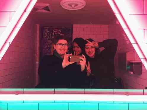 three women taking a selfie in a restaurant bathroom