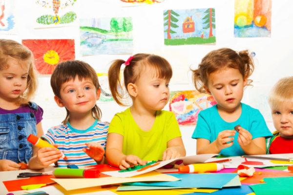 Děti se zabývají prováděním aplikací u stolu
