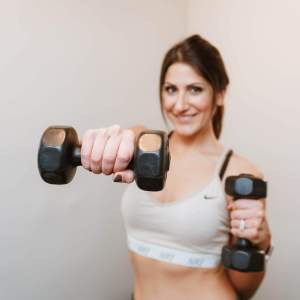 Melly Fit Nutrition - Melly is holding one dumbbell in each hand while extending her left arm forward
