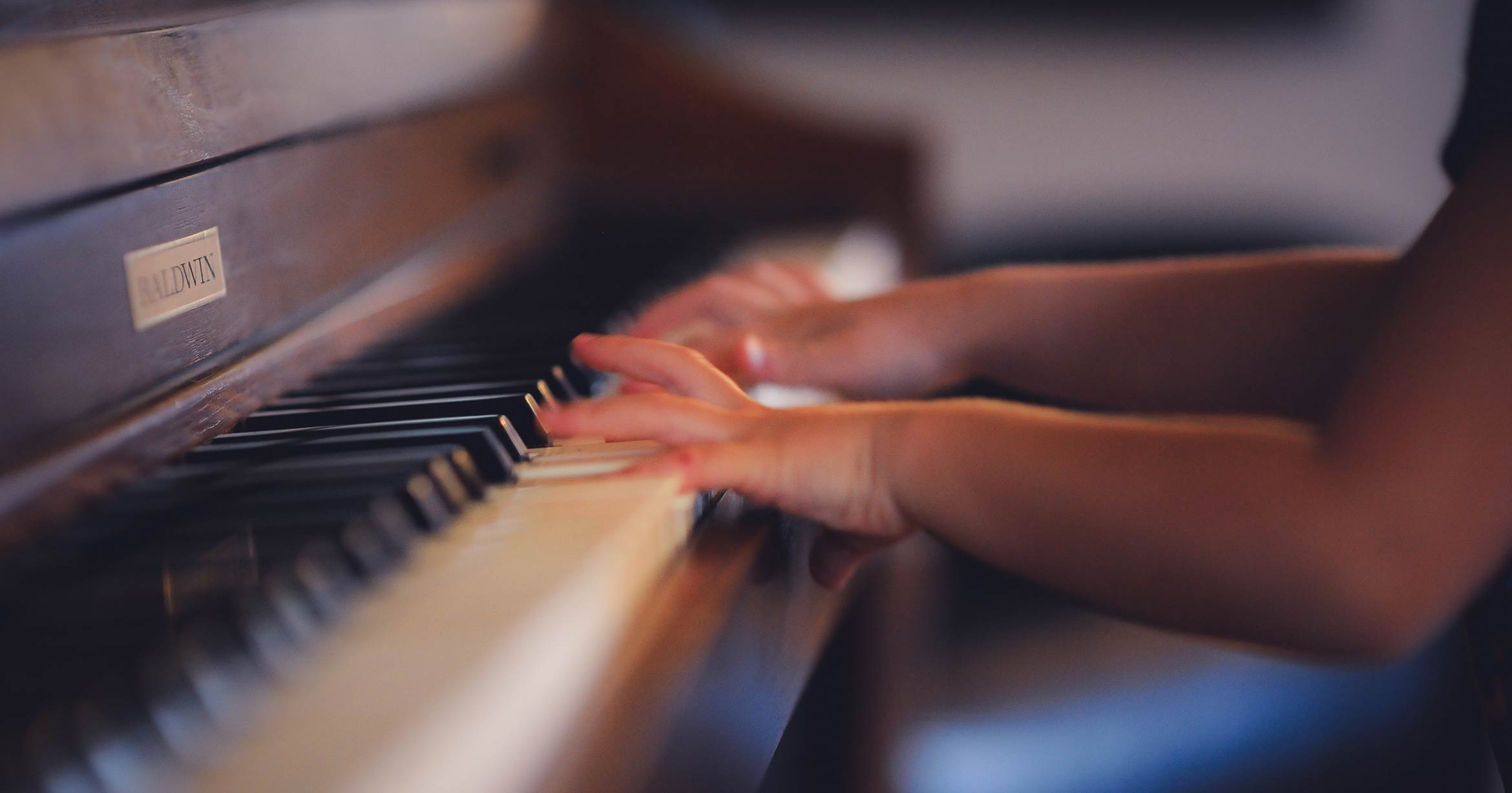 Hands of a child practicing on a piano keyboard