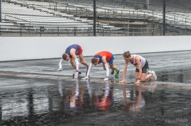 Runners stop to kiss the Yard of Bricks as per race tradition on their lap around the Indianapolis Motor Speedway despite the rain during the Annual OneAmerica 500 Festival Mini-Marathon on Saturday, May 4, 2019.