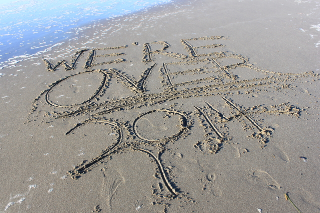 The words WE ARE OVER 2014 written on a beach