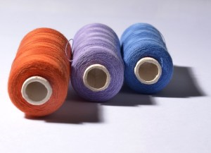 three large spools of thread, one orange, one purple, and one blue, against a white background