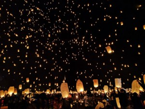 a crowd of people release paper lanterns with candles inside that make them float into the sky. the dark sky is full of small glowing lanterns floating away.