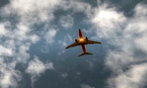 an orange and white jet plane seen from below against a blue sky with fluffy white clouds