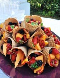 Fruit in een horentje. Neem een ijshoorntje en vul het met verschillende soorten fruit zoals rode besjes op een takje, meloen en aardbeien. Mels Feestje & Tuinfeest hapjes