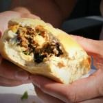 """Een hap uit een gemarineerde hamburgers op de gas BBQ - Hamburger met ui knoflook verse koriander en een plakje gesmolten cheddar kaas op een Italiaanse bol - Mels Feestje en Feest hapjes """""""