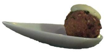 Kikkererwt bitterbal op een amuselepel met een toefje romige zachte mosterdsaus. Een lekker vegetarisch borrelhapje en past perfect bij een glas rode wijn.