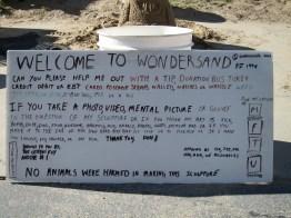 Signboard accompanying weird-cute sand monster.